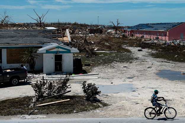 A man cycles passed damaged houses caused by Hurricane Dorian on September 5, 2019, in Marsh Harbour, Great Abaco Island in the Bahamas. PHOTO: AFP