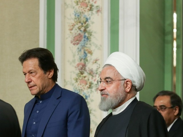 Iranian President Hassan Rouhani walks with Prime Minister Imran Khan as they attend a press conference in Tehran. PHOTO: REUTERS
