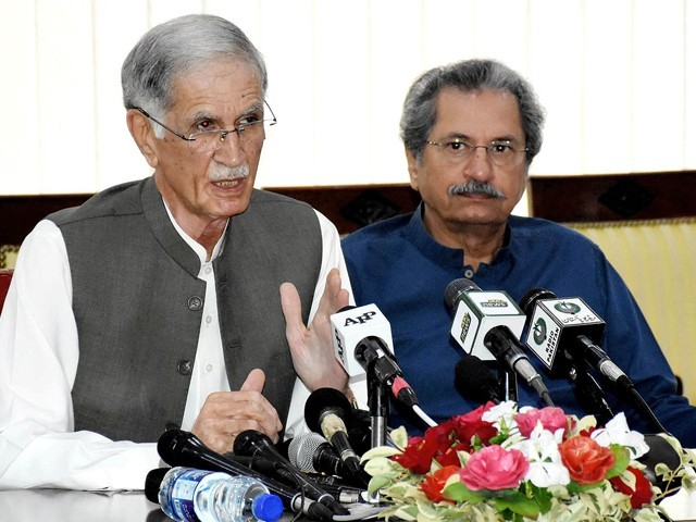 Defence Minister Pervez Khattak and Education Minister Shafqat Mehmood addressing a news conference in Islamabad on Saturday. PHOTO: NNI