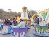 Azadi march participants take a break to enjoy rides at a recreation park in Islamabad. PHOTO: ONLINE