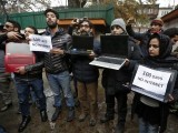 Kashmiri journalists display laptops and placards during a protest demanding restoration of internet service, in Srinagar. PHOTO: REUTERS