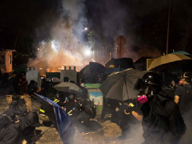 Protesters shelter behind their barricade during clashes with police at the Chinese University of Hong Kong. PHOTO: AFP