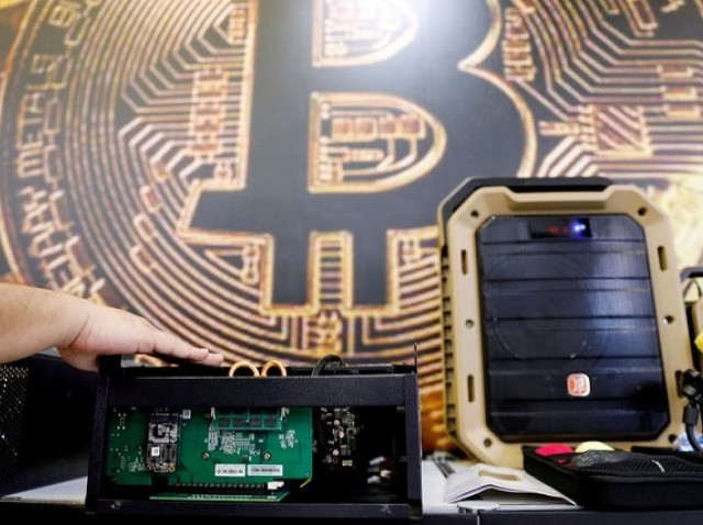 A cryptocurrency mining computer is seen in front of bitcoin logo during the annual Computex computer exhibition in Taipei, Taiwan, June 5, 2018. PHOTO: REUTERS