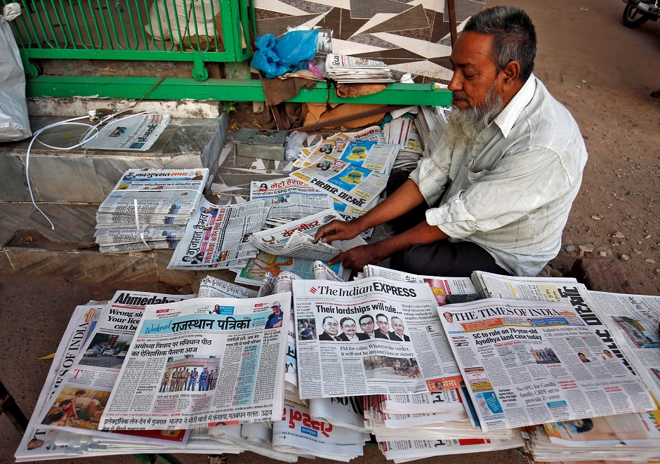 A vendor arranges newspapers with headlines about Supreme Court's verdict on a disputed religious site. PHOTO: Reuters