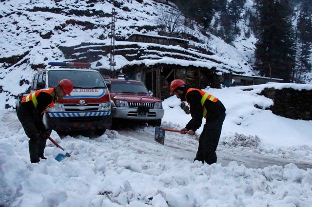 Rescue workers clear a snow-covered road to make way for an ambulance to reach the areas affected by heavy snowfall and avalanches, in Neelum Valley. PHOTO: REUTERS