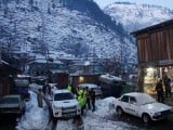 Rescue workers walk the snow-covered road to reach the areas affected by heavy snowfall and avalanches, in Neelum Valley. PHOTO: REUTERS