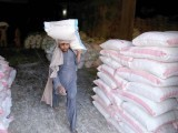 A labourer hauls a sack of wheat flour at a godown in Karachi. PHOTO: INP