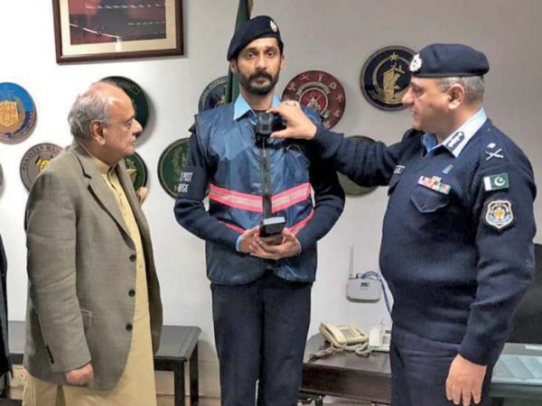 IGP Aamir Zulfiqar briefs Interior Minister Ijaz Shah on the new body cams pinned on police officers. PHOTO: EXPRESS