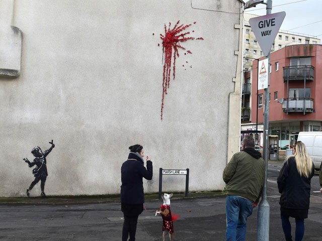 The graffiti shows a young girl in a headscarf with a catapult and a splatter of red flowers. PHOTO: REUTERS