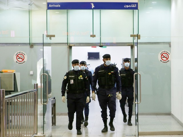 Kuwaiti policemen wearing protective masks wait at Sheikh Saad Airport in Kuwait City, on February 22, 2020, before transferring Kuwaitis arriving from Iran to a hospital to be tested for coronavirus.PHOTO: AFP