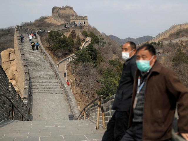 Men wearing protective masks stand as people hike along a section of the Great Wall in Badaling in Beijing, on its first day of re-opening after the scenic site's coronavirus related closure, China, March 24, 2020. PHOTO: REUTERS