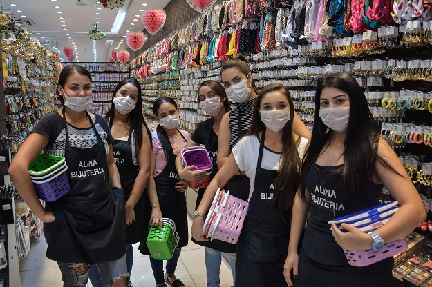 Shop sellers pose as they wear face masks as a preventive measure against the spread of the new coronavirus. PHOTO: AFP