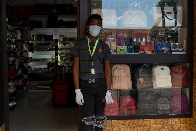 A shop attendant wears gloves and a mask while waiting for customers outside a shop in Windhoek. PHOTO: AFP
