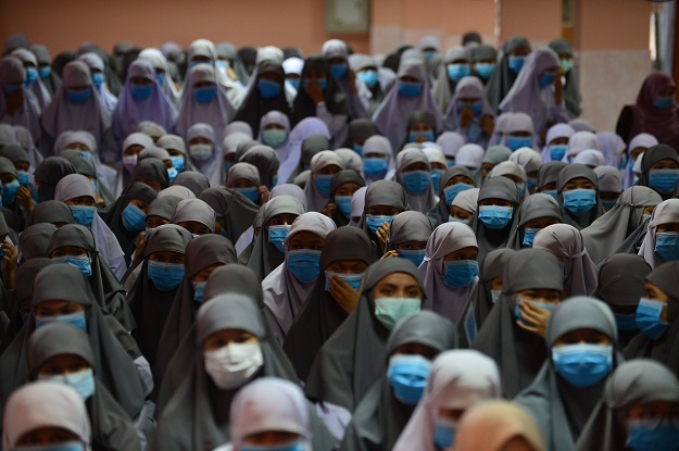Thai Muslim students wear face masks donated by a school official as a preventive measure against the COVID-19 coronavirus during a ceremony in Thailand. PHOTO: AFP