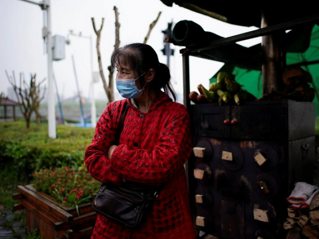Li Yu, 55, a peddler selling corn, wears a face mask at an ancient city wall in Jingzhou, after the tourist attraction reopened as the lockdown was eased in Hubei province, the epicentre of China's coronavirus disease (COVID-19) outbreak, March 26, 2020. PHOTO: REUTERS