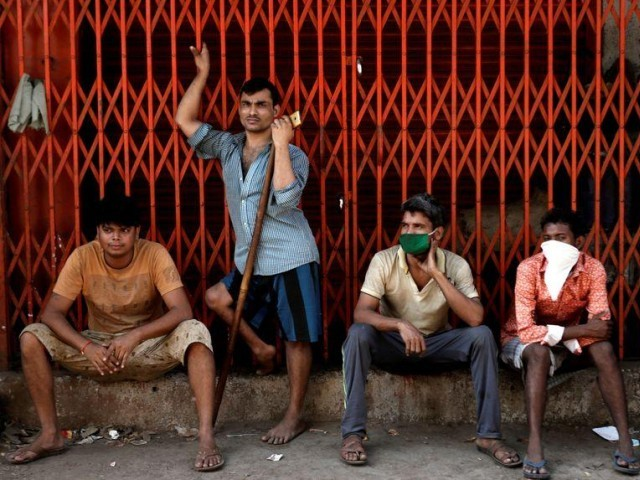 Migrant workers, who work in textile looms, are seen outside a loom after it was shut due to the 21-day nationwide lockdown to slow the spread of the coronavirus disease, in Bhiwandi on the outskirts of Mumbai, India, April 1, 2020. PHOTO: REUTERS