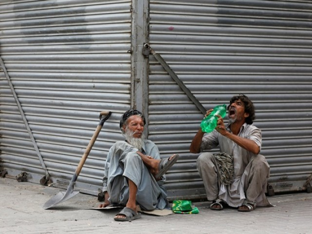FILE PHOTO: Daily wage laborers, wait for work as they sit outside closed shops, during lockdown amid the outbreak of coronavirus disease (COVID-19), at a market in Karachi, Pakistan April 14, 2020. REUTERS