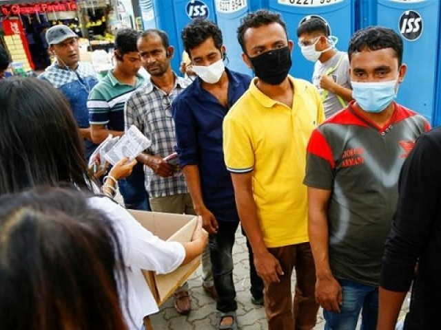 Migrant workers, mostly from Bangladesh, queue to collect free masks and get their temperatures checked, in Singapore (Photo: Reuters)