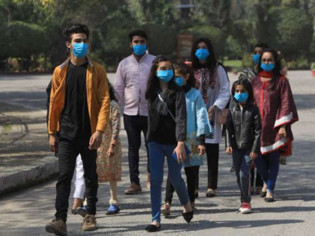 Volunteers wear masks as a preventive measure against the coronavirus, as they walk during an awareness compaign by a NGO at the premises of the St John Cathedral in Peshawar. PHOTO: Reuters