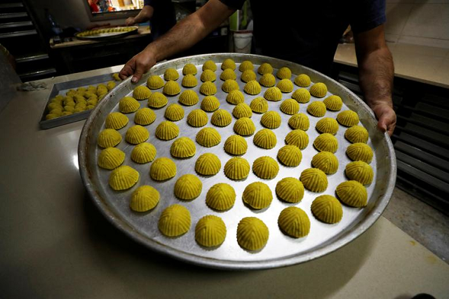 A worker shows traditional sweets as Palestinians prepare for the upcoming holiday of Eidul Fitr marking the end of Ramazan at a bakery in Jerusalem's Old City. PHOTO: Reuters