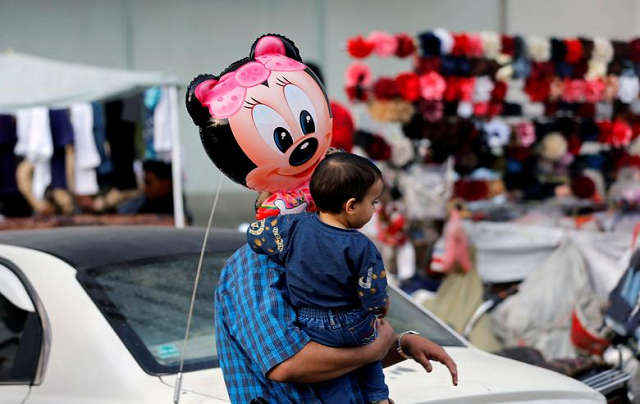 A man carries his son who holds a balloon outside a shopping mall ahead of Eidul Fitr holiday in Sanaa, Yemen. PHOTO: Reuters