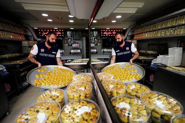 A worker places freshly-made traditional sweets as Palestinians prepare for the upcoming holiday of Eidul Fitr marking the end of Ramadan at a bakery in Jerusalem's Old City. PHOTO: Reuters