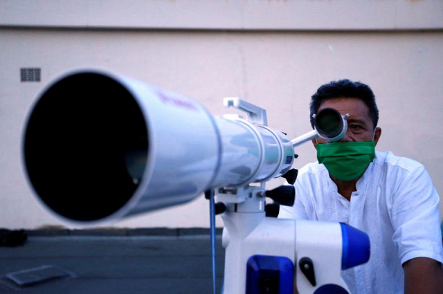 An official wearing a protective mask uses a telescope to view the moon on the roof of the Ministry of Religious Affairs building to mark the Eidul Fitr celebrations in Jakarta, Indonesia. PHOTO: Reuters