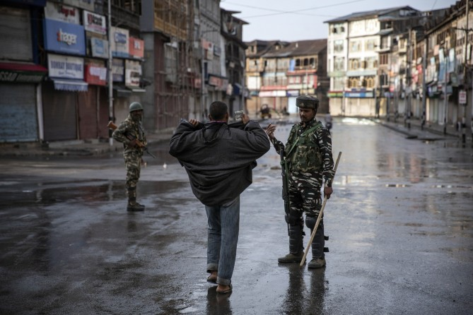 An Indian paramilitary soldier orders a Kashmiri to open his jacket before frisking him during curfew in Srinagar, Indian controlled Kashmir, Aug. 8, 2019. The beautiful Himalayan valley is flooded with soldiers and roadblocks of razor wire - Dar Yasin. Photo: Pulitzer.org