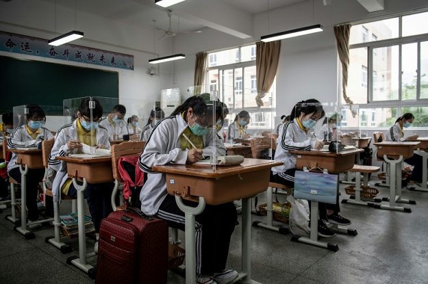 High school senior students study with plastic partitions in a classroom in Wuhan in China's central Hubei province. PHOTO: AFP