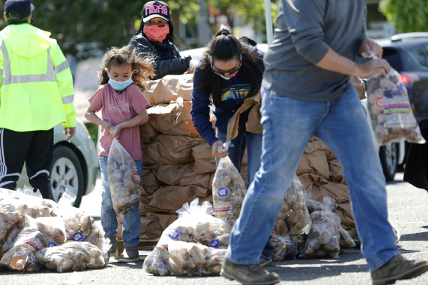 The Reed family in Pasco, Washington, hands out potatoes donated by Washington famers who are giving away a million pounds of excess stock they have as a result of the food service industry slowdown. PHOTO: AFP
