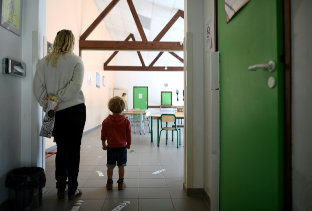 A mother and son stand near glued-on arrows set up to mark social distancing measures at an elementary school a few days before its reopening, in Clairefontaine-en-Yvelines, near Paris. PHOTO: AFP